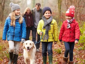 Family walking in the woods with dog