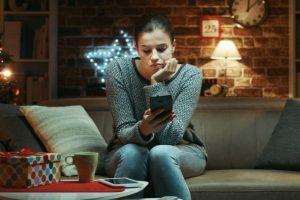 Woman alone at christmas looking at her phone looking sad