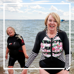 Two women in wet suits coming out of the sea