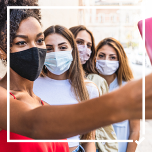 A group of women take a selfie with their masks on