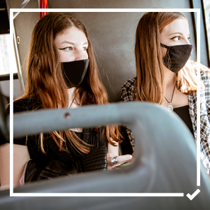 Two young girls on a bus wearing masks